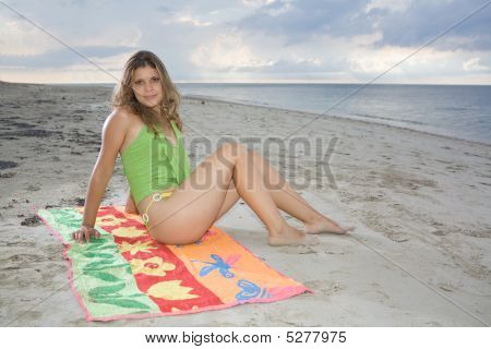 Attractive Lady Sitting On A Towel In The Beach
