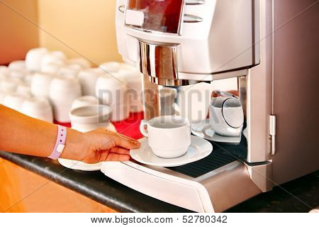 Waitresses hand with coffee machine at cafeteria .