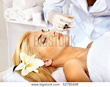Doctor woman giving botox injections. Isolated.