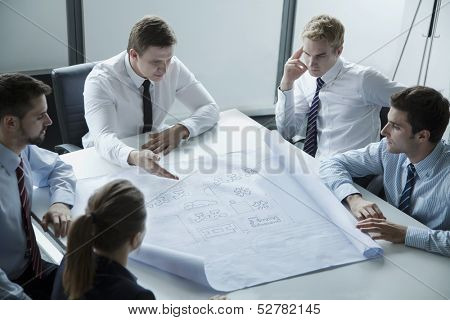 Five architects discussing and planning over a blueprint