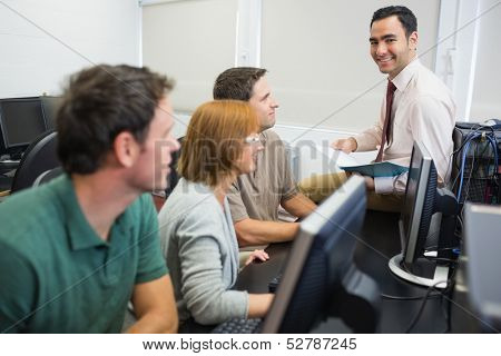 Portrait of a smiling teacher with mature students in the computer room
