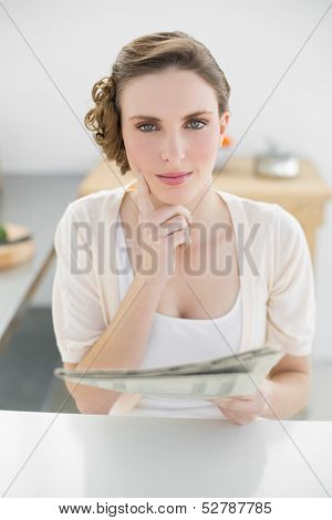 Gorgeous thinking woman sitting in her kitchen holding newspaper looking seriously at camera