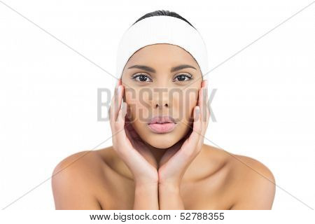 Unsmiling nude brunette with hairband touching face on white background