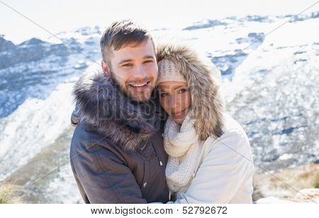 Portrait of a loving couple in jackets embracing in front of snowed mountain range