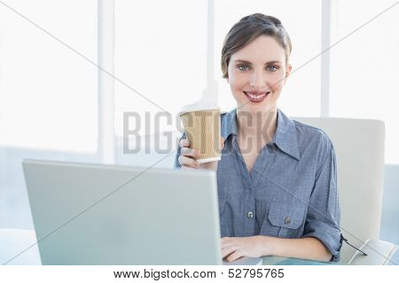 Calm beautiful businesswoman showing disposable cup while sitting at her desk in front of her notebook