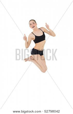 Euphoric slim model jumping in the air on white background