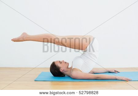 Full length side view of a young woman doing the Plough posture on exercise mat