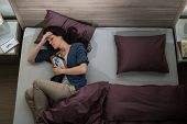 stock photo of obituary  - Lonely woman lying in bed missing her dead husband - JPG