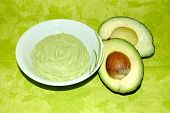 picture of avocado  - a bowl of avocado cream with avocado fruit on green background - JPG