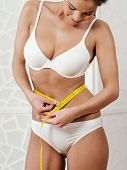 stock photo of measurement  - Photo of a slim young woman in her underwear measuring her waist with a tape measure - JPG