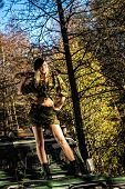 foto of machete  - Beautiful girl on camouflage outfit with machete she standing top of the off-road vehicle bonnet