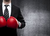 stock photo of punch  - businessman in boxing gloves on gray background - JPG