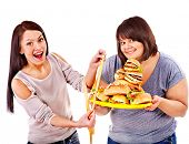 picture of high calorie foods  - Woman holding fast food and measuring tape - JPG
