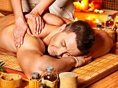 stock photo of therapist massage  - Man getting massage in bamboo spa - JPG
