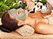 stock photo of beauty parlour  - Beautiful woman having clay facial mask apply by beautician - JPG