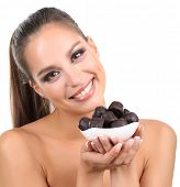 Portrait of beautiful young girl with chocolate candies isolated on white