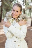 stock photo of shivering  - Cute woman shivering while having a walk in a forest on a winter day - JPG