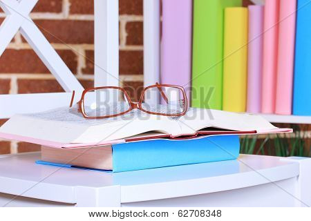 Composition with glasses and books, on chair, on cabinet and wall background