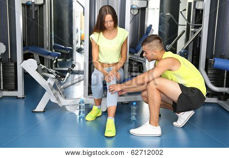 Guy help girl at gym