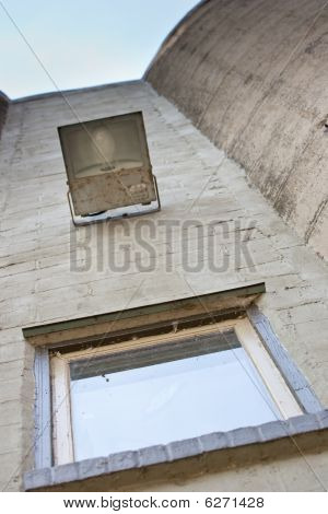 Looking Up At Old Concrete Structure With Outdoor Lamp