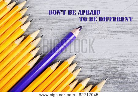 Celebratory pencil among usual pencils, on wooden background