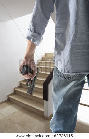 Man holding gun against an stairs background