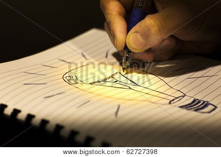 concept of idea: writing a light bulb in a copybook