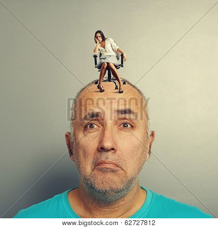 sad man and small despondent woman on his head over grey background