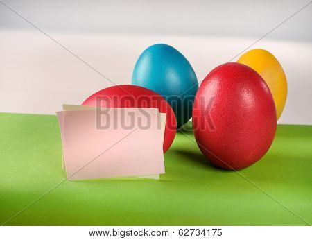 Colorful Easter eggs and blank paper notes.