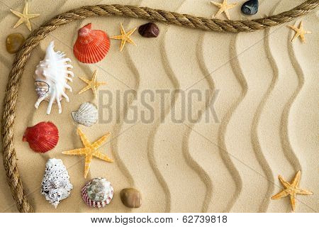 Pebbles And Seashells On Rippling Sand With A Rope