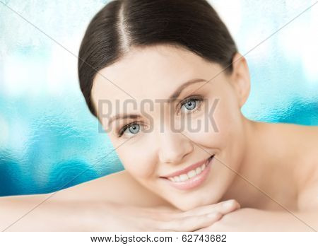spa, vacation and resort concept - smiling woman in spa salon lying on the massage desk