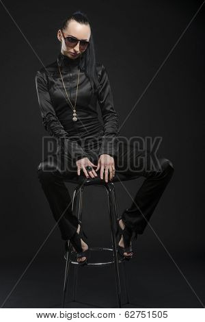 Full length shot of beautiful Caucasian woman wearing black bodysuit and sitting on a posing stool, against black background