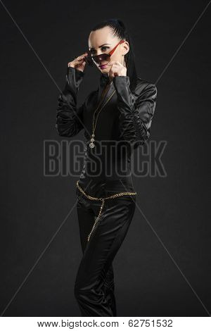 Portrait of beautiful Caucasian woman putting on sunglasses and wearing black bodysuit against black background