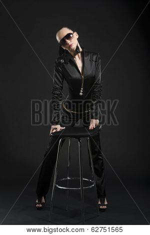 Full length shot of intimidating Caucasian woman wearing black bodysuit and sunglasses, against black background