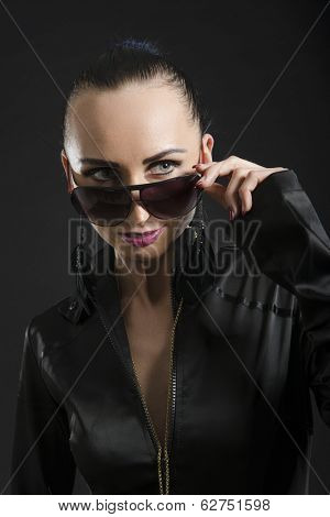 Headshot of beautiful Caucasian woman wearing black bodysuit and looking over sunglasses, against black background
