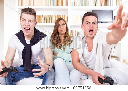 Bored Women Between Two Casual Passionate Men Playing Video Game With Joystick