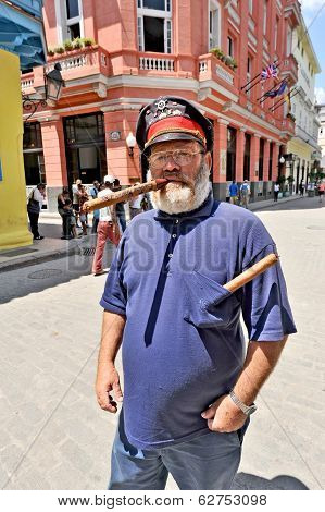 An old man standing on a street with a huge cigar