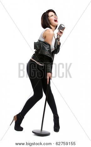Full-length portrait of rock musician wearing leather jacket and handing static mic, isolated on white. Concept of rock music and rave