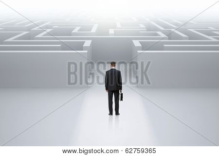 Full-length backview portrait of businessman with case standing in front of maze. Concept of leadership and difficulties