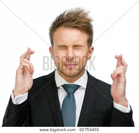 Half-length portrait of businessman with fingers crossed and eyes closed, isolated on white