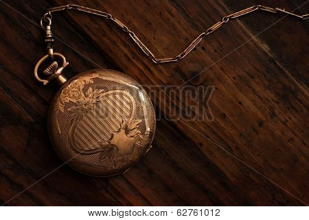 Antique pocket watch on rustic dark wood background with copy space.  Low key still life with directional natural lighting for effect.