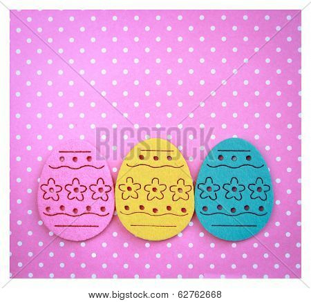 Decorated felt easter eggs yellow, blue and pink on a pinky polka dots background