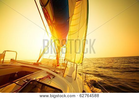 Sail boat in an open sea at sunset