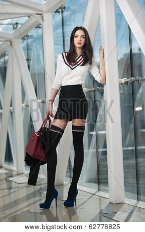 Sensual elegant woman in office outfit posing in a modern scenery. Beautiful and sexy brunette