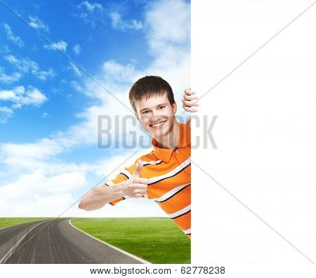 Teenage boy with a blank banner over the road and sunny sky. Hitch-hiking concept.