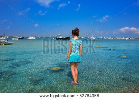 Kid girl walking at formentera in Estany des Peix lake rear view