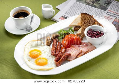 Breakfast With Two Eggs, Bacon, Beans, Tomatoes, Mushrooms And Coffee On Green Napkin And Newspaper
