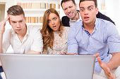 stock photo of pissed off  - shocked and frustrated casual group of friends sitting on couch looking at laptop pissed off friends cheering on computer - JPG