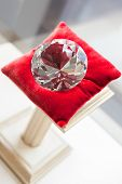 foto of jewel-case  - Close up of large diamond on red pillow at jeweler - JPG