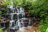 pic of upstream  - Small river water pouring over rocky ledge waterfall in countryside  during summer rain seasons - JPG